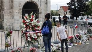 Des gens se recueillent avec des fleurs et des bougies devant l'église de Saint-Etienne-du-Rouvray, en Normandie, au lendemain d'une attaque ayant causé la mort d'un prêtre.