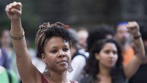 Des femmes lèvent leur poing en l'air lors d'un rassemblement à Montréal pour dénoncer la mort d'Abdirahman Abdi.