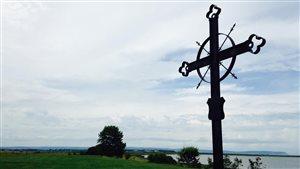 Une croix se dresse près d'un cours d'eau