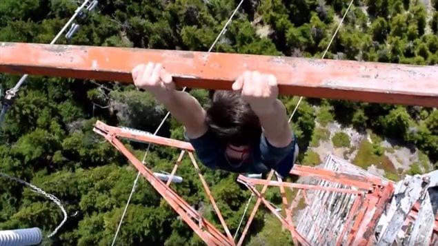 Un jeune suspendu à un pylône électrique