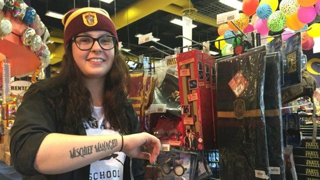 Entourée de marchandises à l'effigie de Harry Potter, Toni Smith, 23 ans, exhibe son tatouage sur lequel on peut lire « Mischief Mannaged », un titre de la bande originale du film «Harry Potter et le prisonnier d'Azkaban», le 30 juillet 2016, à Winnipeg.