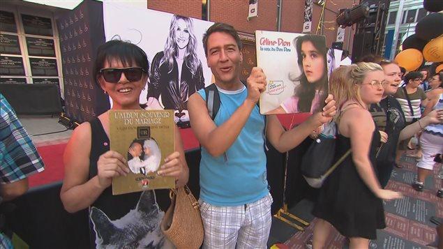 Des fans de Céline Dion se tiennent sur le tapis rouge et montrent des pochettes d'album de la chanteuse avant son spectacle au Centre Bell de Montréal, le 31 juillet 2016.