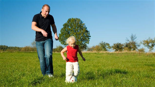 Un père joue au ballon avec sa fille