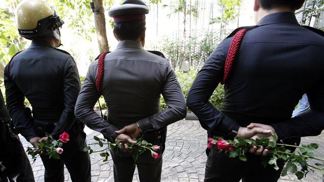Des policiers thaïlandais tiennent des roses données par des partisans pro-armée.