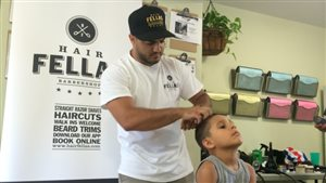 Un enfant se fait couper les cheveux gratuitement grâce à l'initiative d'Ibrahim Musa.