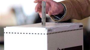une main vote dans une urne