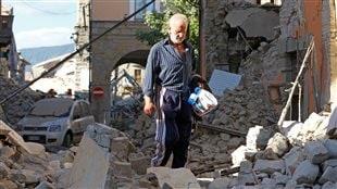 Un homme marche dans les décombres à la suite du tremblement de terre d'Amatrice.