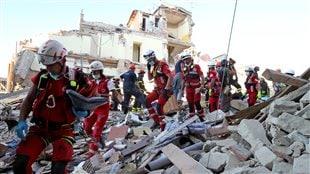 Des secouristes marchent à travers les décombres à Amatrice, au centre de l'Italie.