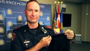 Le sergent major Rob Patterson du Service de police de Calgary a entre les mains un hijab spécialement conçu pour être porté avec l'uniforme.