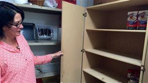 La bénévole Alanna Pettigrew montre les étagères vides de la banque alimentaire de Banff.