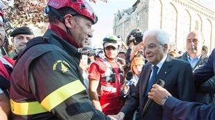 Le président Sergio Mattarella serre la main d'un pompier qui participe aux recherches à Amatrice.
