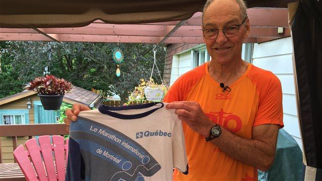 Laurent Bouchard qui tient le t-shirt de son premier marathon, qui remonte à 1979.