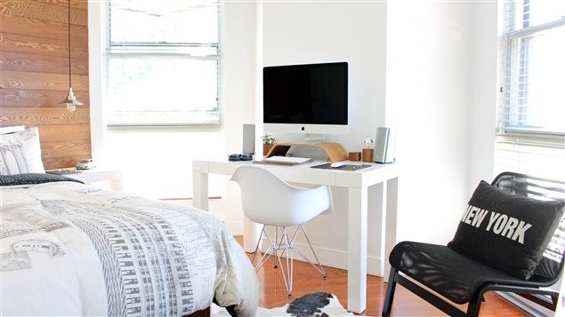 L'intérieur d'une chambre avec un lit, une chaise, un bureau de travail et un ordinateur