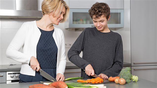 Une mère et son fils cuisinent ensemble.