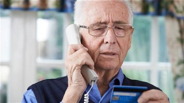 Une personne âgée divulgue son numéro de carte de crédit par téléphone.