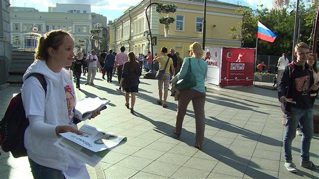 Des jeunes tentent de distribuer des journaux d'un parti d'opposition à des gens dans une rue de Moscou, mais peu de passants sont intéressés.