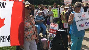 Des gens manifestent contre le programme d'éducation sexuelle de la province devant Queen's Park.