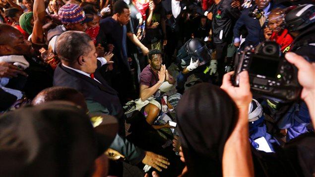 Des gens encerclent une personne blessée à la suite d'une altercation.