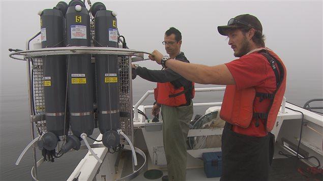 Les techniciens Michel Rousseau et Félix St-Pierre préparent la rosette avant qu'elle ne plonge dans le Saint-Laurent.