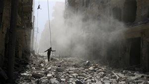 Un homme marche sur les débris des immeubles détruits, après des bombardements dimanche à Alep.