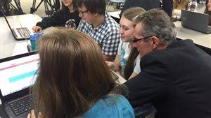 Le premier ministre Brian Pallister est assis devant un ordinateur, entouré d'élèves du Collège Beliveau, à Winnipeg.