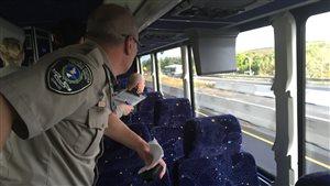 Des policiers de la SQ observent les automobilistes fautifs à bord d'un autobus.