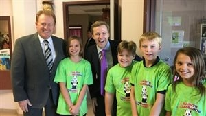 Le premier ministre Brian Gallant en compagnie du ministre de l'Éducation, Brian Kenny et d'élèves de l'école Park Street de Fredericton, où il a fait son annonce.
