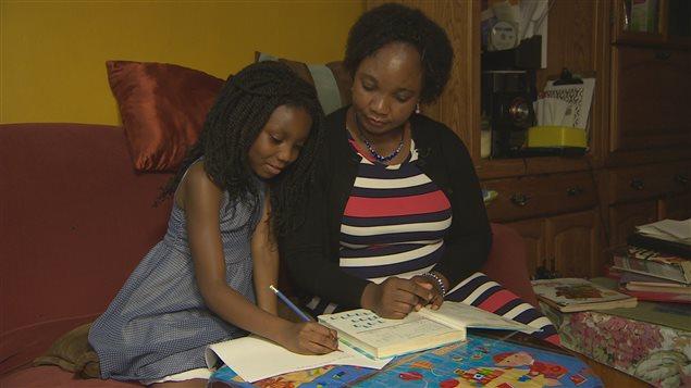 Annie Mponda aide sa fille à faire ses devoirs.