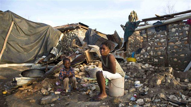 Au milieu des ruines de Jérémie, en Haïti, une femme et un enfant sont assis sur des seaux, dans ce qui était autrefois leur maison.