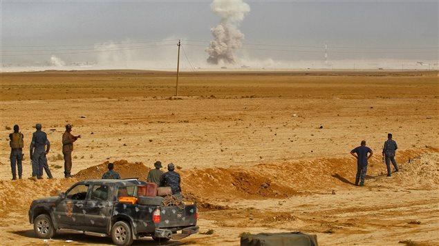 Des soldats irakiens positionnés à environ 45 km au sud de Mossoul observent une colonne de fumée qui s'échappe d'un village.