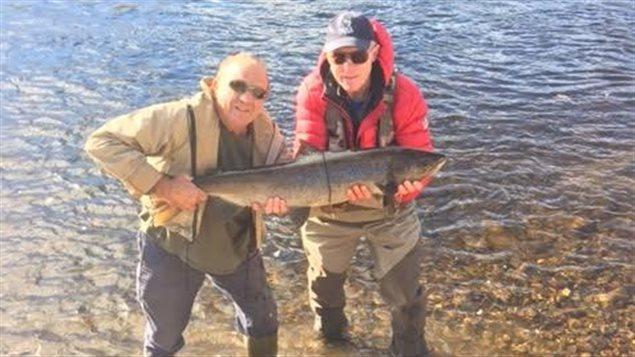 Deux pêcheurs tiennent dans leurs bras un saumon géant