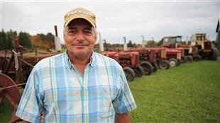 Réjean Beaudry devant une partie de sa collection de tracteurs à Verner en Ontario