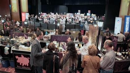 Dans une salle de congrès, une foule s'arrête à différents kiosques de dégustation.