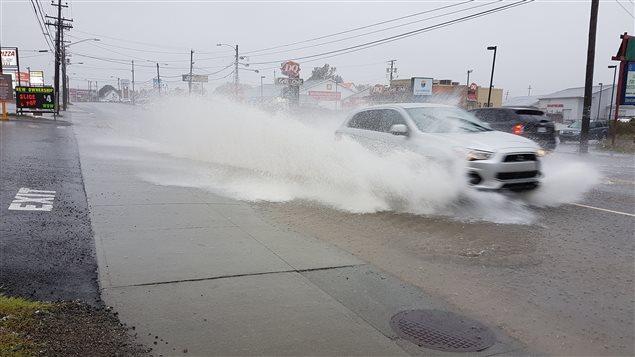 Des voitures circulent dans une rue inondée