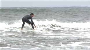 Un homme fait du surf à Sept-Îles.