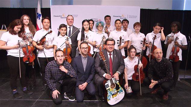 Robert Dumas, de Sun Life Québec, le maire de Montréal et trois membres du groupe Simple Plan entourés de jeunes musiciens