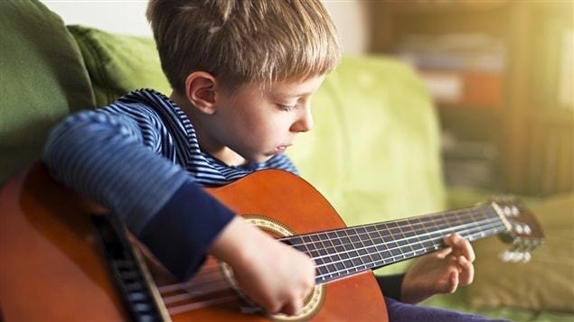 Un garçon joue de la guitare