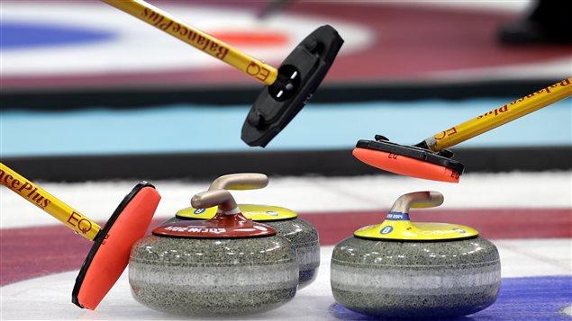 Deux pierres jaunes et une rouge dans la maison, lors d'un tournoi de curling