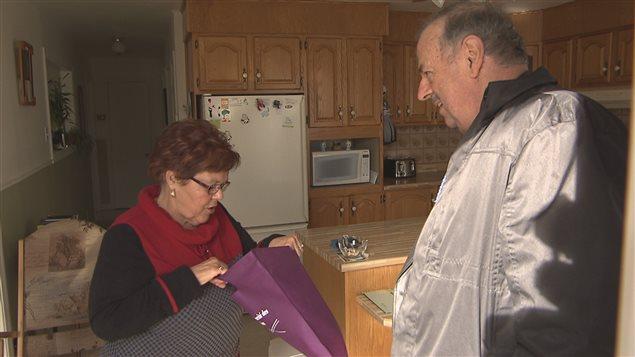 Simon Brunelle, maire de Sainte-Cécile-de-Lévrard, distribue des trousses d'information à des personnes aînées de sa municipalité.