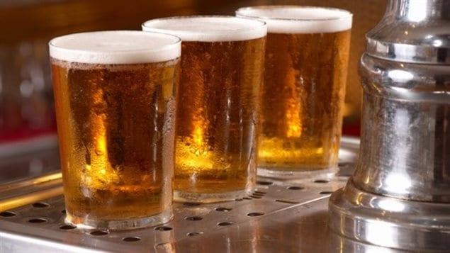 Gros plan sur trois verres de bière reposant sur le comptoir d'un bar.