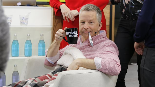 André Robitaill est assis dans un fauteuil avec un thermomètre dans la bouche.