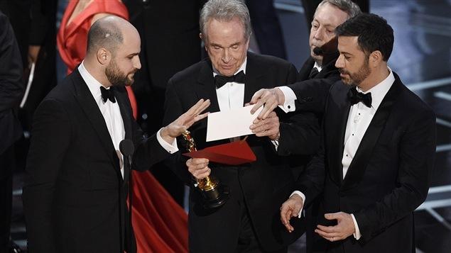 Le producteur de « La La Land » Jordan Horowitz, le présentateur Warren Beatty et l'animateur Jimmy Kimmel regardent l'enveloppe annonçant « Moonlight » comme meilleur film aux Oscars, le 26 février 2017