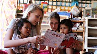Des bénévoles apprennent à lire l'anglais à deux enfants cambodgiens.