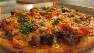 Une pizza garnie de boeuf, carottes et pesto d'épinards