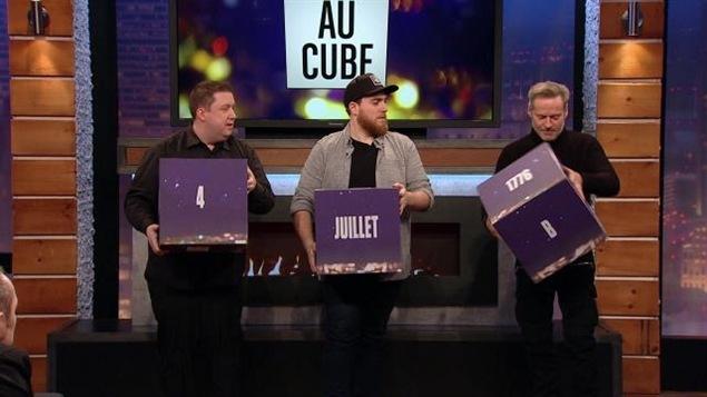 Le participant, Phil Roy et Luc Guérin tiennent de gros cubes dans les mains.