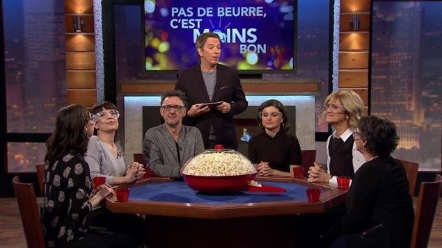 Les participants sont assis à une table sur laquelle trône un immense bol de pop corn.