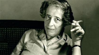 Hannah Arendt, tenant une cigarette, est accoudée sur une chaise.