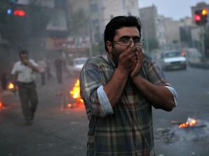 Un manifestant tente de se protéger des gaz lacrymogènes, à Téhéran.