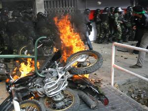 Une motocyclette des forces de l'ordre incendiée par les manifestants.