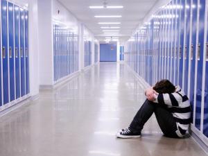 Jeune homme assis dans un couloir d'école